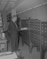 Man looking at cards in the Library at Mankato State College, 1962-01-07.