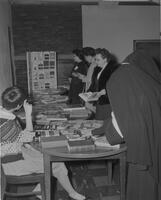 Women overlooking books on display at the Language Conference at Mankato State College, 1962-12-04.