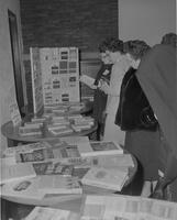 Women looking at books on display at the Language Conference at Mankato State College, 1962-12-04.