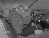 A female student in her car at Mankato State College, 1963-01-16.