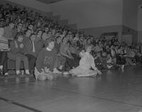 Jo Schiller and Jan Lothert cheerleading at a Wresting match at Mankato State College, 1963-01-18.