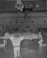 One man on trampoline at Gymnastics meet at Mankato State College, 1963-01-28.