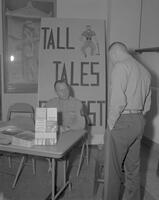 Two Marines at a military information table in front of a sign for a tall tales contest at Mankato State College, 1963-01-22.