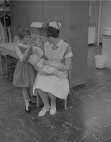 "Connie Loeffler demonstrating proper baby care (how to dress a head wound) to a ""little mother"" Mankato State College 1963-01-28"