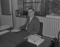 Mankato State College President Clarence L. Crawford seated at desk. 1963-01-28