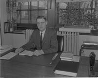 Mankato State College President Clarence L. Crawford seated at desk, take two.  1963-01-28.