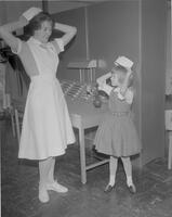 Connie Loefler showing little girl how to put on a nurse's cap. Mankato State College. 1963-01-28