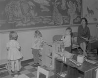 Student supervising children's activity in child development class. Mankato State College. 1963-01-29