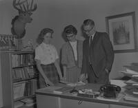 Professor with two students looking at papers on his desk at Mankato State College, 1963-01-29.