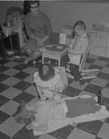 Child Development student supervising children playing doctor at Mankato State College, 1963-01-9-29.