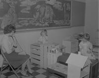 Child Development student playing house with children at Mankato State College, 1963-01-29.