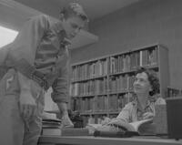 Ellie McKinney, a reference librarian at Mankato State College, seated at desk and helping a student, 1963-02-13.