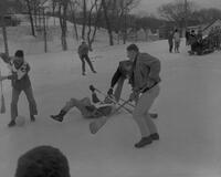Students playing broom ball during Snow Week at Mankato State College, 1963-02-23.