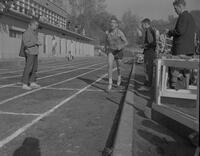 Track athlete, M. Bryan, finishing race, Mankato State College, 1961-10-23.