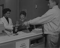 Norma Dick, a student at Mankato State College, working with J. Ramserran behind circulation desk in library, 1961-10-30.
