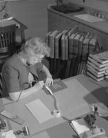 Alice Hughes, acting Library Assistant, working on processing a book in the library, 1961-10-30.