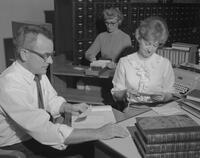 Mr. Frayne Anderson, a Serials Librarian, working behind the circulation desk at Mankato State College, 1961-10-30.