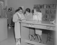 Three women looking at call cards at Mankato State College, 1961-11-01.