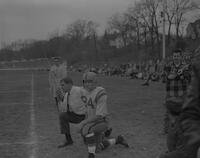 Coach Otto and Marlin Amos kneeling along sideline, Mankato State College, 1961-11-17.