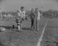 Jim Seidel showing two boys how to grip a football at Mankato State College, 1961-11-13.