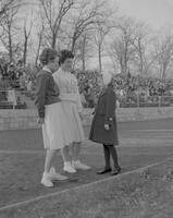 Mankato State College cheerleaders Judy Opfer and Jeanette Peinartz talking to child at Football game, 1961-12-05.