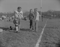 Jim Seidel showing two young boys how to hold a football at Mankato State College, 1961-12-05.
