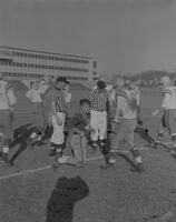 Players and Referees on sideline during N. Dakota Football game at Mankato State College, 1961-12-05.
