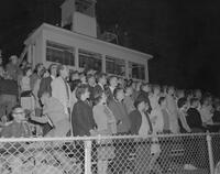 Students standing for school song at a football game, Mankato State College, 1961-11-08.
