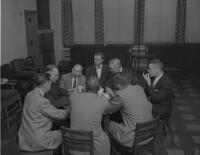 Eight men having coffee and conversation around a table. Mankato State College. 1961-12-12.