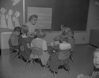 Student teacher reading to group of small children at Wilson Campus School, Mankato State College, 1962-02-02.