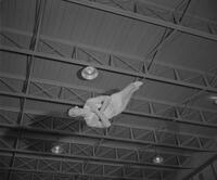A gymnast does a flip in midair. 1961-12-12. Mankato State College.
