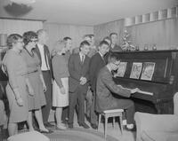 Students gathered around a piano at the Russian Club Christmas party. Mankato State College. 1962-01-02.