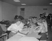 Students cutting and gluing paper in a classroom. Mankato State College. 1962-01-02.