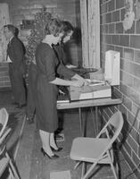 Lynn Phillips loading records on record player at Phi Beta Lambda Christmas party, Mankato State College. 1962-01-02.