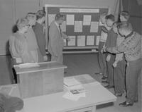 Members of the Mankato State College along with Mr. Hatfield checking a bulletin board, 1962-01-12.