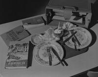 Textbooks lying on table along with ashtrays and dirty dishes, yearbook photo for Mankato State College, 1962-01-15.