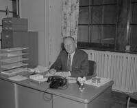 Mankato State College Director of Special Services, Arden E. Hesla, at desk, 1962-01-15.