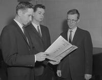 Three men looking at sheet music, Mankato State College, 1962-01-02