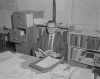 William B. Lass, Assistant Professor of History at Mankato State College, reading a book at his desk.