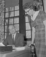 Gentleman seated at desk, having a discussion with a woman at Mankato State College, 1962-01-15.