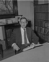 Thomas L. Moir sitting at his desk at Mankato State College, 1962-01-15.