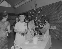 Ladies gathered around a dessert and punch table at an unknown event, 1962-05-21.
