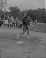 A female Mankato State College Student batting a softball at the All-College picnic, 1962-05-21.