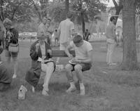 A pair of Mankato State College Students seated on a bench eating their food at the All-College picnic, 1962-05-21.
