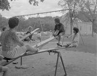 Mankato State College students playing on teeter-totters and swings at All-College picnic, 1962-05-21.