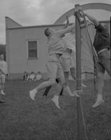 Male Mankato State College students playing volleyball at the All-College picnic, 1962-05-21.