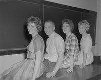 A posed photograph of four Mankato State College students seated on a desk in front of a chalkboard, 1962-05-25.