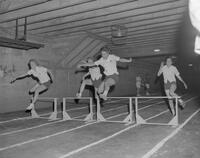 Running hurdles in the girls track intramurals competition by the Mankato State College Physical Education Department, 1962-05-25.
