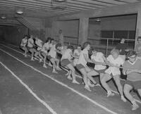 Mankato State College girl's tug-o-war during Physical Education Department intramural track meet, 1962-05-25.