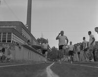 Men running on track at Mankato State College, 1962-06-06.